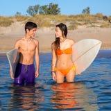 Los pares felices de la persona que practica surf del adolescente en la playa apuntalan Foto de archivo