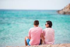 Los pares felices de las vacaciones que se relajan en la arena blanca y la turquesa prístina riegan en la playa en Grecia Fotos de archivo libres de regalías