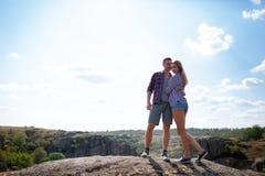 Los pares felices de turistas descansan en las montañas Un par cariñoso se sienta en una montaña y disfruta de una hermosa vista imagenes de archivo
