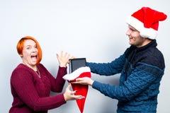 Los pares felices del Año Nuevo de la Navidad celebran día de fiesta dan emo de los regalos Foto de archivo