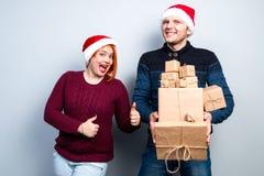 Los pares felices del Año Nuevo de la Navidad celebran día de fiesta dan emo de los regalos Imagenes de archivo
