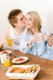 Los pares felices del desayuno disfrutan de beso romántico Imagen de archivo libre de regalías