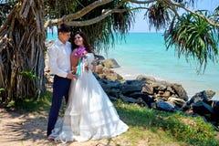 Los pares felices del recién casado en amor se están colocando en la playa Boda y luna de miel en las zonas tropicales en la isla fotografía de archivo