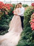 Los pares felices en amor caminan en el jardín enorme Fotos de archivo libres de regalías