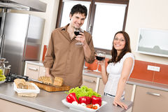 Los pares felices en cocina moderna beben el vino rojo foto de archivo libre de regalías