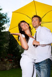 Los pares felices en el verano llueven con el paraguas Imagen de archivo libre de regalías