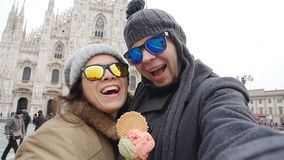 Los pares felices en Milán que come el helado que toma la foto del autorretrato del selfie el vacaciones viajan en Italia Vacacio metrajes