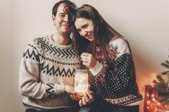 Los pares felices en los suéteres elegantes que sostienen la linterna se encienden en festiv Imagenes de archivo