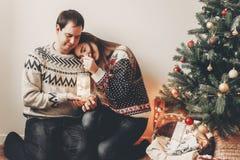 Los pares felices en los suéteres elegantes que sostienen la linterna se encienden en festiv Fotos de archivo libres de regalías