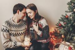 Los pares felices en los suéteres elegantes que sostienen la linterna se encienden en festiv Fotos de archivo