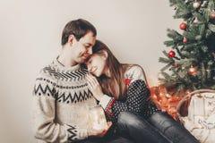 Los pares felices en los suéteres elegantes que sostienen la linterna se encienden en festiv Imagen de archivo