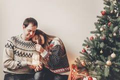 Los pares felices en los suéteres elegantes que sostienen la linterna se encienden en festiv Foto de archivo libre de regalías