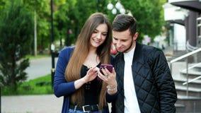 Los pares felices hacen compras en línea vía el teléfono, eligen mercancías, hacen compras almacen de video