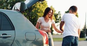 Los pares felices han llegado al paseo del verano de las vacaciones por el coche Salga el equipaje del coche metrajes