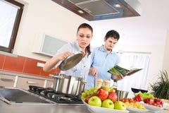 Los pares felices jovenes cocinan en cocina con el libro de cocina Imágenes de archivo libres de regalías