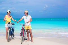 Los pares felices jovenes con las bicis en la playa del verano vacation Fotografía de archivo