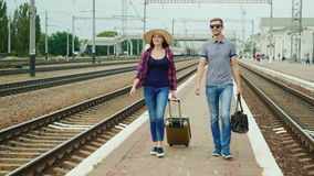 Los pares felices jovenes de turistas con los bolsos del viaje van a lo largo del peron a lo largo del ferrocarril Comenzar un gr metrajes