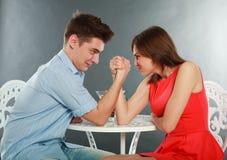 Los pares felices jovenes desafían luchar en pulso en la tabla Imagen de archivo