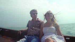 Los pares felices jovenes en gafas de sol se sientan en la deriva del barco de madera que disfruta de sus vacaciones Cámara lenta metrajes