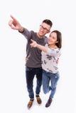 Los pares felices jovenes hermosos del inconformista aman el sonreír abrazando el finger del punto para vaciar el espacio de la c Fotografía de archivo