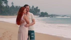 Los pares felices jovenes que abrazan en el océano varan en la puesta del sol metrajes