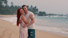 Los pares felices jovenes que abrazan en el océano varan en la puesta del sol almacen de metraje de vídeo