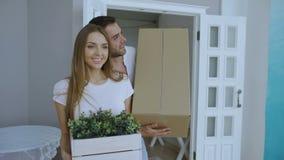 Los pares felices jovenes que caminan en nueva casa después de día móvil y se besan metrajes