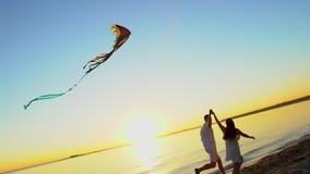 Los pares felices jovenes que juegan con una cometa en el mar varan en la puesta del sol Hombre y mujer que disfrutan del tiempo  metrajes