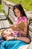 Los pares felices jovenes se relajan en parque del banco Fotografía de archivo libre de regalías