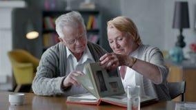 Los pares felices mayores gastan tiempo juntos y al nostálgico ellos que miran el álbum y la sonrisa de foto viejo metrajes