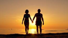 Los pares felices que caminan a lo largo de un mar varan llevar a cabo las manos en un fondo de la puesta del sol almacen de metraje de vídeo
