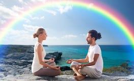 Los pares felices que meditan en loto presentan en la playa Foto de archivo libre de regalías