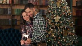 Los pares felices que sostienen bengalas acercan al árbol de navidad metrajes