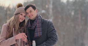 Los pares felices que sostienen las tazas de té calientes durante invierno ajardinan Pares jovenes en amor en vacaciones del invi almacen de video