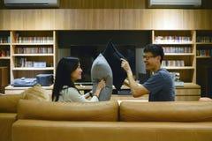 Los pares felices se golpearon con las almohadas en sala de estar en la noche fotos de archivo