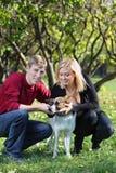 Los pares felices se ponen en cuclillas y tocan el perro en parque Foto de archivo libre de regalías