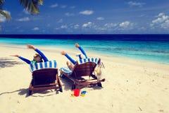 Los pares felices se relajan en una playa tropical Imagen de archivo libre de regalías