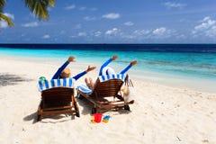 Los pares felices se relajan en una playa tropical Fotos de archivo