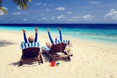 Los pares felices se relajan en una playa tropical Imagen de archivo