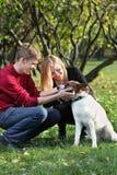 Los pares felices sonríen y tocan el perro en parque Imagenes de archivo