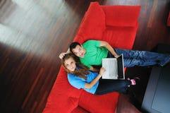 Los pares felices tienen la diversión y trabajo sobre la computadora portátil en el país Foto de archivo