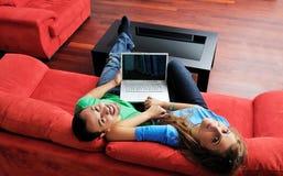 Los pares felices tienen la diversión y trabajo sobre la computadora portátil en el país Fotografía de archivo