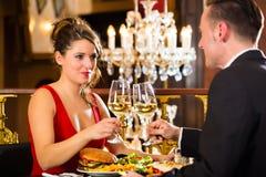 Los pares felices tienen una fecha romántica en restaurante Imagenes de archivo