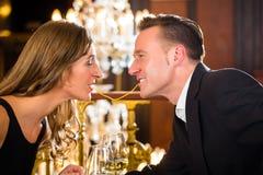Los pares felices tienen una fecha romántica en restaurante imagen de archivo