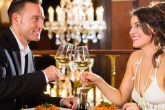 Los pares felices tienen una fecha romántica en restaurante Imagen de archivo libre de regalías
