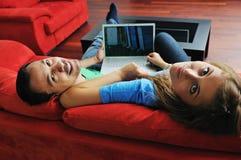Los pares felices trabajan en la computadora portátil en el país Fotos de archivo