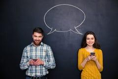 Los pares felices usando los teléfonos móviles sobre la pizarra con discurso burbujean Fotografía de archivo