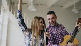 Los pares felices y cariñosos divertidos bailan en la cama que canta con el regulador de la TV y que toca la guitarra El hombre y foto de archivo