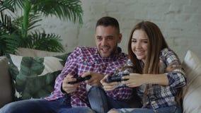Los pares felices y cariñosos jovenes juegan al juego de la consola con el gamepad y se divierten que se sienta en el sofá en sal metrajes