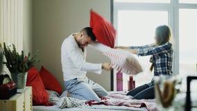 Los pares felices y cariñosos jovenes luchan las almohadas en cama en casa por la mañana fotografía de archivo libre de regalías